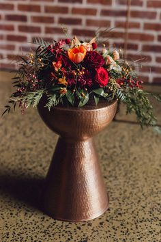 Beaten copper pedestal with autumn toned burgundy and orange flowers for modern industrial wedding ceremony | Raconteur Photography