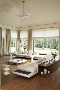 canapés blancs, commode en bois et suspension originale dans le salon moderne