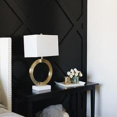 A gold ring lamp sits on a black console table placed in front of a black paneled accent wall beside a light gray linen wingback bed. - A gold ring lamp sits on a black console table placed in front of a black panele. Black Accent Walls, Black Walls, Black Accents, Wall Accents, Accent Wall Bedroom, Bedroom Decor, Bedroom Lamps, Wall Decor, Black Nightstand