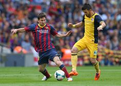 Lionel Messi of FC Barcelona holds off a challenge from David Villa of Club Atletico de Madrid during the La Liga match between FC Barcelona and Club Atletico de Madrid at Camp Nou on May 17, 2014 in Barcelona, Catalonia.