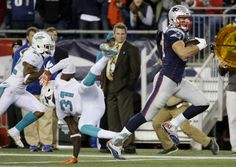 New England Patriots tight end Rob Gronkowski (87) runs past Miami Dolphins free safety Michael Thomas (31) as he heads to the end zone for a touchdown in the first half an NFL football game, Thursday, Oct. 29, 2015, in Foxborough, Mass. (AP Photo/Steven Senne)