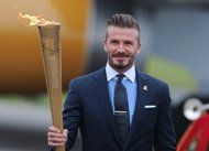 David Beckham carries the Olympic torch as it arrives at RNAS Culdrose air base in Cornwall, May 18. Sailor Ben Ainslie was the first torchbearer as the Olympic flame began its 70-day journey around Britain and Ireland on Saturday ahead of the 2012 London Games. (AFP Photo/Carl Court)
