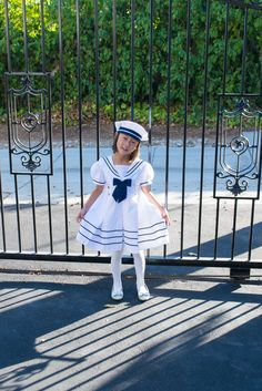 Pleated skirt with brass anchor buttons, piping along hemline, short puffed sleeves, and nautical collar. A matching bow in front and big bow ties in the back give it a classic nautical look. Zipper back closure ensures an easy fit. Beret hat with contrasting trim and white satin ribbon bow complete this adorable sailor dress outfit for girls! http://shop.winnietriplets.com/listing/466175716/sailor-dress-with-hat