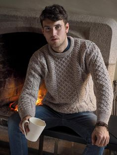 This Mens Aran Crew Neck Sweater the most famous style in Aran Knitting. This Aran Sweater can be worn by both men and women. It incorporates a variety of Irish Aran Stitches that were believed to bring luck, success, and health to the wearer. Honeycomb stitch indicating the hard working honey bee, and Aran basket stitch to bring the omen of good luck, and the diamond to bring wealth. Warmth is the key to this style and made with 100%  merino wool it is sure not to let you down.