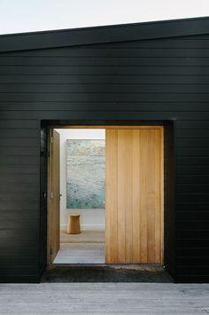Black house with wooden door.