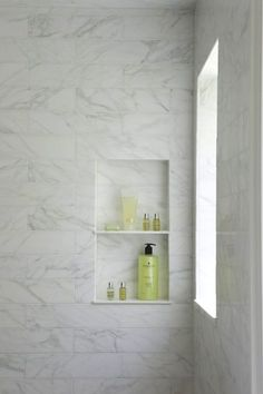 Calcutta marble tiled shower with window and built-in shelves.