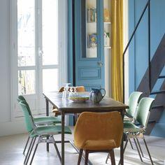 Une salle à manger aux airs rétro. Le salon fait aussi office de salle à manger. L'escalier en métal créé sur mesure mène à la chambre de Madeleine, 15 ans, nichée sous les toits.