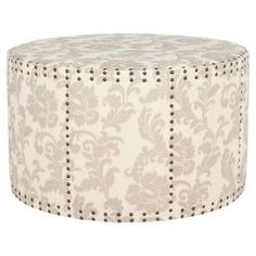 """Round ottoman with nailhead detailing and acanthus leaf-print upholstery.  Product: OttomanConstruction Material: Plywood and fabricColor: Taupe and beigeDimensions: 20.1"""" H x 33.9"""" Diameter"""