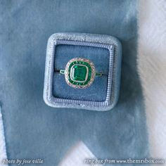 Breckenridge USD 25,000, vintage-inspired platinum, emerald and diamond ring. Centering a bezel set 1.64ct Cushion Cut emerald, this ring is accompanied with a GIA Certificate of Colombian origin with minor clarity enhancements (F1). The center stone has no visible inclusions to the naked eye. Breckenridge is surrounded by a halo of eighteen Calibre Cut emeralds and thirty Rose Cut diamonds, finished off with four Rectangular Cut emeralds on the shoulders of the ring.
