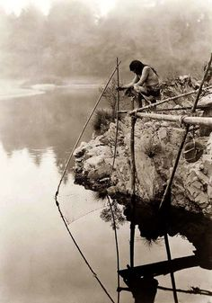 You are viewing an impressive image of an Indian Fishing From a Platform. It was taken in 1923 by Edward S. Curtis.  The picture shows a Hupa Indian on a platform over the water using a fishing net. This is a great picture of this Indian Custom