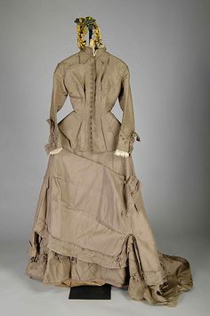 The Metropolitan Museum of Art's 1876 Wedding dress is made of silk and has a colored top resembling a jacket with a draping skirt and a ruffle underlay.