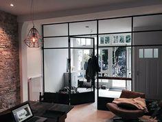 Een industrieel interieur met verouderde bakstenen wand en zwart stalen puien die een ruimtelijke hal creëren. Een stoer en hip stadsappartement. #simplysteel #industrieelinterieur