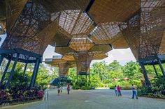 People wander under an intricate wood art installation with green trees in the background
