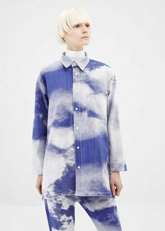 Oversized, long-sleeved button up blouse in a blue and white sky-patterned cotton blend. Spread collar. Snap closure placket with white painted snaps. Slanted patch pocket at chest. Hem lower in rear. Embroidered cloud pattern throughout in white. Minimum machine wash warm, and dry in shade, or dry clean.