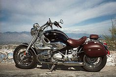 Black and burgundy BMW R1200C motorcycle with mountains in the background