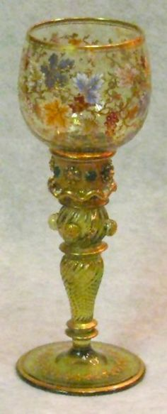 A Moser glass goblet, baluster stem in green, polychrome grapes and leaves, stem with gold Coralene and jeweled cabochons. Czechoslovakia, circa 1893-2008