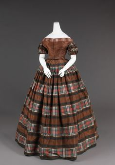 An early 1850s evening dress from the US. The large horizontal stripes  on the skirt and the use of plaid are very characteristic of the 1850s.