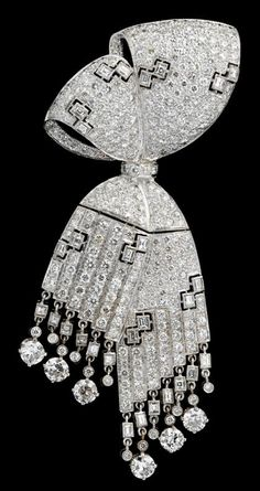 Platinum and diamond bow brooch   Double knot cascading articulated bow, displaying over two hundred and thirty petite pave set diamonds, followed by seventy-five round cut diamonds of slightly larger size amongst sixteen petite baguette cut diamonds. Brooch finishes in articulated diamond fringe. Total diamond weight approximately 6.75 carats.