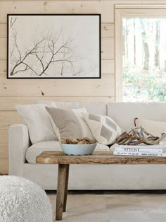A Room and Board sofa and CB2 pouf gather round an antique pine bench in this white living room.