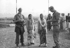 Dutch soldiers control the papers of javanese women in a transitcamp of the Sevens December Division near Tandjong Priok (or of another division from camp Doeri on Batavia). Date: 09-1946 - 10-1946