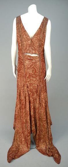 TRAINED METALLIC BROCADE EVENING GOWN, EARLY 1930s (back view) Sleeveless rust silk with dusty rose and gold lame floral, having applied bands to bodice, cutout at center back waist and gored skirt with handkerchief point hem and fishtail train. Unlabeled.  - whitakerauction