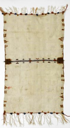 Africa | Cape / shawl from the Anti Atlas Mountain region, Morocco |  Wool; The cream ground woven with cream stripes and dashes, dyed with henna motifs along the long borders, the central section divided by a band of woven and embroidered decoration with terracotta and blue wool bobbles, the end borders similarly decorated
