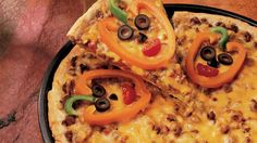 Kids will love veggies when you make jack o'-lantern faces with the veggies on top of yummy pizza!