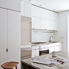 An all-white kitchen reflects plenty of natural light.