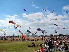 Families at kite festival in Portsmouth, Hampshire, England on sunny summer day.