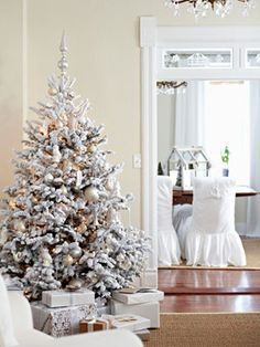 A flocked Christmas tree decorated in all white.