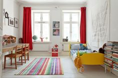 A brightly colored rug, yellow bed frame, and red curtains and I forgot that the walls are white