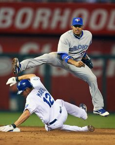 KANSAS CITY, MO - APRIL 21: Shortstop Yunel Escobar #5 of the Toronto Blue Jays makes a leaping throw over Mitch Maier #12 of the Kansas City Royals at Kauffman Stadium on April 21, 2012 in Kansas City, Missouri. The Blue Jays defeated the Royals 9-5. (Photo by Tim Umphrey/Getty Images)