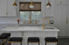 Contemporary white kitchen features Ryan Saghian Collection Olivier Barstools placed in front of a white island topped with a white marble countertop fitted with a stainless steel undermount prep sink and a brass gooseneck faucet lit by three Small Hicks Pendants.