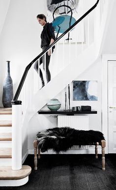 Modern entryway with wooden bench and black faux fur throw