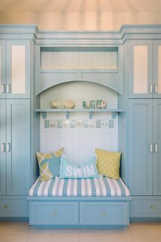 Blue mudroom features blue lockers painted Benjamin Moore Marlboro Blue flanking a blue mudroom bench fitted with drawers topped with a blue and gray striped cushion situated below a blue shelf and corbels an overhead cubby illuminated by a beaded semi flush mount light.