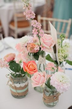 Soft pink/pale pink dahlia and roses table centre piece using jam jars with lace. From 'A Seafoam Green and Soft Coral Inspired Colourful Wedding'. Photography by http://www.tarahcoonan.com/
