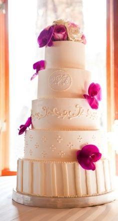 Beautiful classic cream fondant cake with monogram & magenta orchids.
