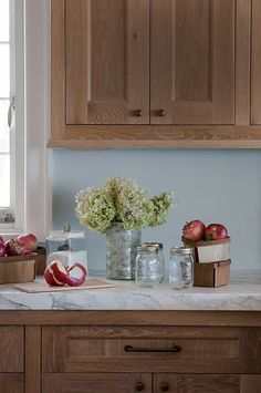 Classic kitchen countertop: wooden cabinets, marble countertop, mason jars & apples.