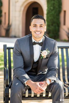 San diego beach wedding at admiral kidd club groom charcoal grey tuxedo with black lapel and white dress shirt with black bow tie and black vest with white floral boutonniere and black watch sitting down