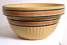 Here is a nice antique yellowware mixing bowl with rust and blue bands around it. It measures 10.5 inches wide by 5.5 inches high and is not marked. This bowl has the usual crazing and a small glaze p