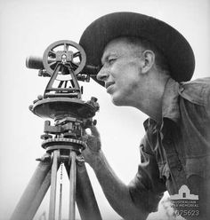 Markham valley, New Guinea. 1944-08-28. VX74093 bombardier T.J.C. Holtz of the survey section, 4th Field Regiment, using a theodolite while surveying a new area near the camp.