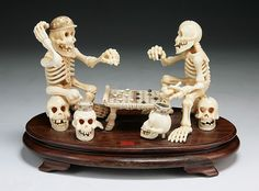 """A Japanese Antique Carved Ivory Okimono Skeleton Group: depicting the scene of skeletons playing checkers while seating on top of other skeleton heads, circa 1900  Dimensions: H: 6-1/2""""; W: 10-1/2"""""""