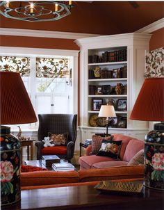 Living Room - Benson Interiors  Boston, Ma  www.bensoninteriors.com #livingroom #interiordesign #red #chair #couch #lamps #windowtreatments #woodtrim #bookcase #white #chandelier #flowers
