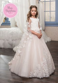 This Niagara flower girl dress with a detachable cape is a masterpiece! Luxurious lace and tulle gown features a sleeveless bodice adorned with flowers. Matching flowers add a touch of elegance to the