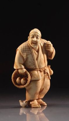 Finely incised Japanese delicately carved netsuke figure, depicting a standing man carrying a basket and eggs, a chick at his feet, early 20th century period, artist's signature to the base. Size; Height of netsuke carving is 2 inches.