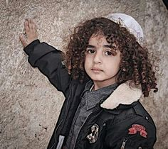 ~ A young Jewish boy donned with kippah at the Western Wall (kotel).  This wall is what remains of the Temple that Shlomo built for ELOHIM.  Love those gorgeous curls! ~