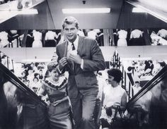 Troy Donahue of television's 'Surfside Six' is followed by fans of the escalator.