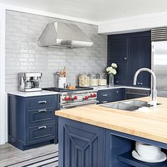 To offset the modern surfaces of this kitchen designer Paige Schnell topped the island with rock maple butcher block for an organic contrast. | Coastalliving.com