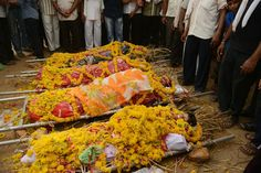 DECORATED IN DEATH: The bodies of a family were draped in flowers near their house before being taken to a crematorium in Bavla, India, Monday, after they committed suicide. Five family members attempted suicide by drinking poison, police said, but one member survived. (Sam Panthaky/AFP/Getty Images)