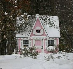 quaint pink cottage in the snow.